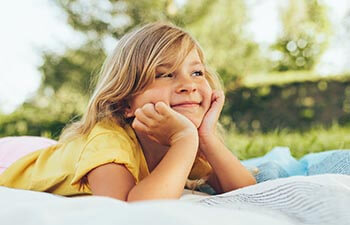 Cheerful child relaxing on a blanket in the park and enjoying summertime