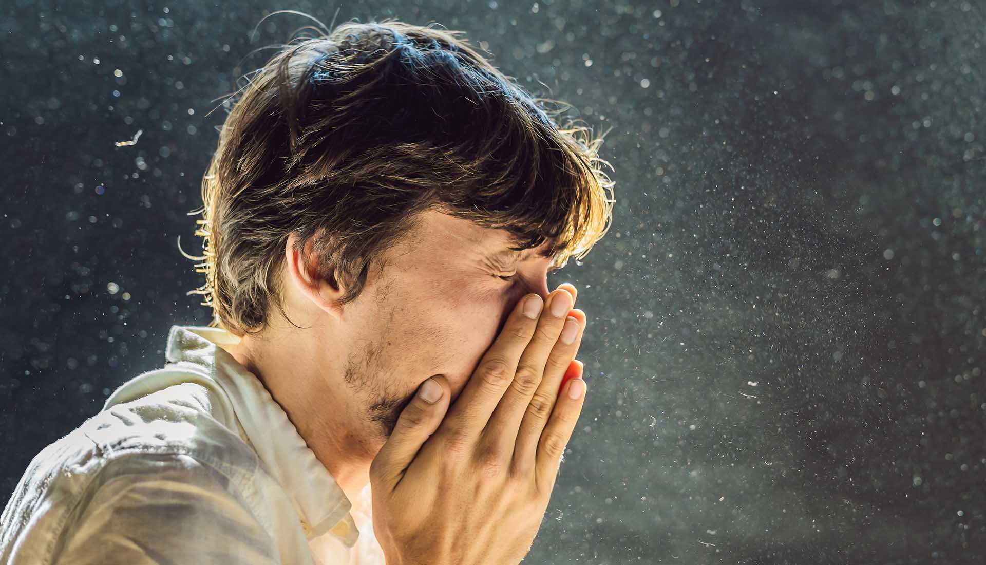 man with closed eyes covering his nose with hands while sneezing because of dust