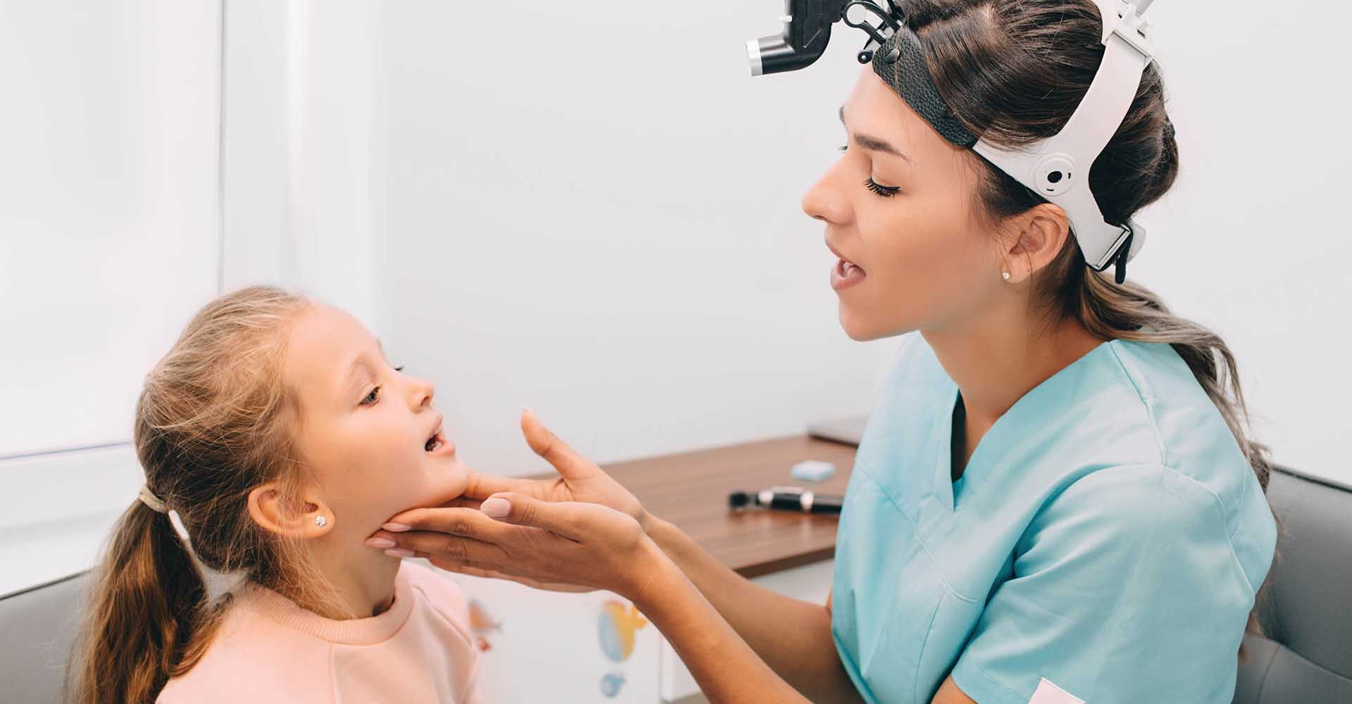 ENT doctor examining mouth of little girl at clinic